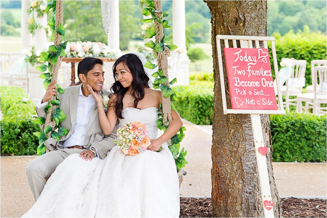 beautiful bride & groom sat on a swing at their wedding in Watford, Hertfordshire
