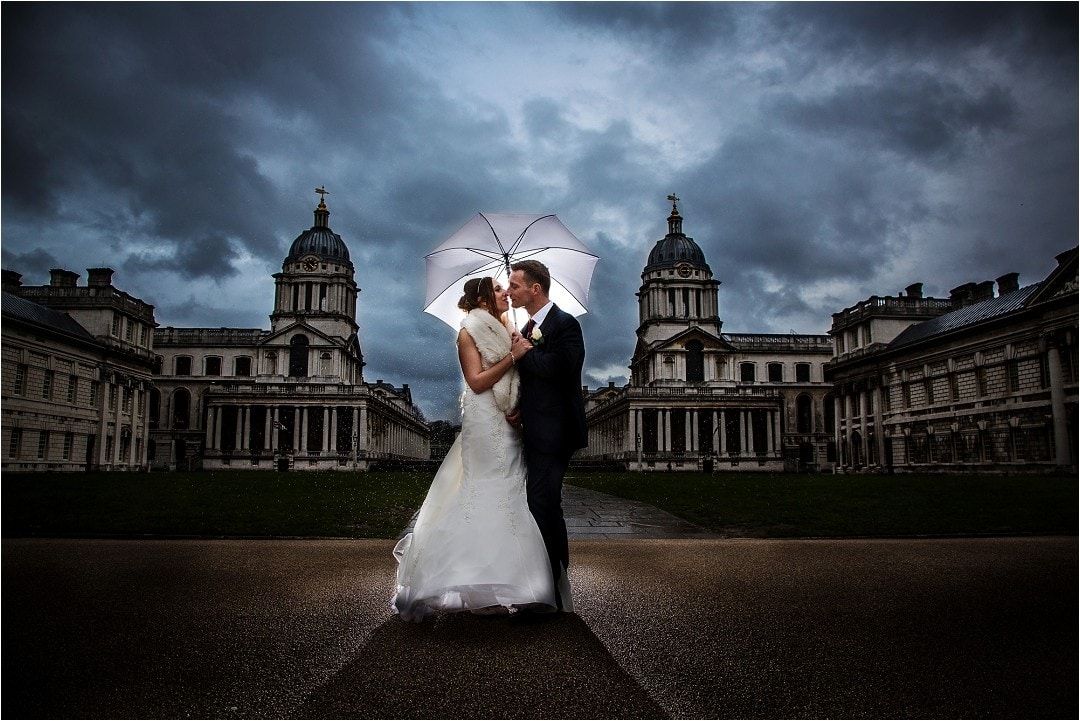 Old Royal Naval College wedding photograph with bride & groom stood under umbrella with stormy skies above them