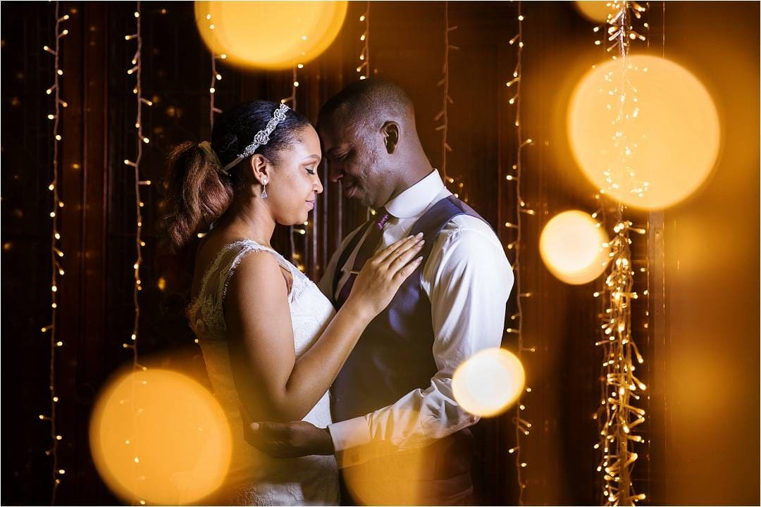 Bride and groom stood under some twinkle lights after their wedding in Hertfordshire