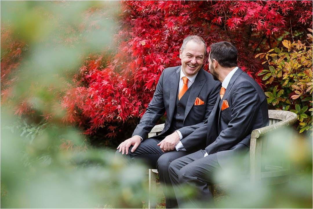 Photograph of grooms at their Hertfordshire wedding sat on a bench with beautiful autumn colours