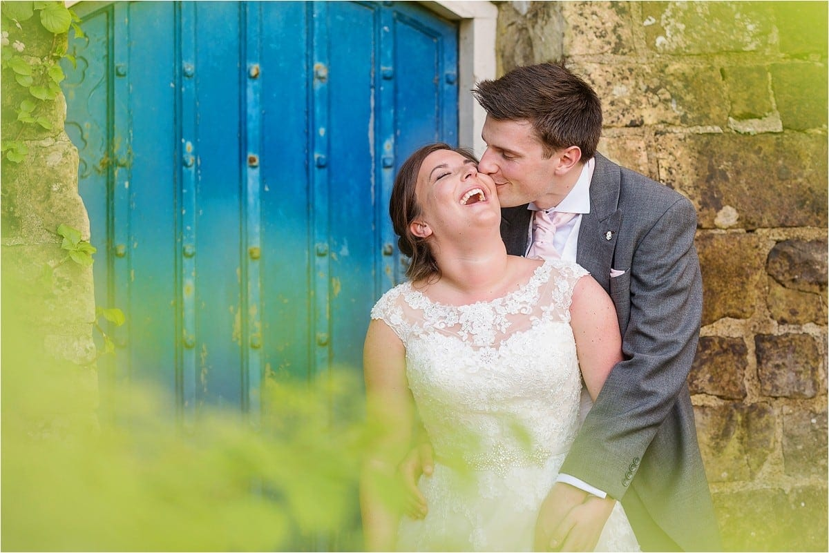 Groom kissing bride whilst she is laughing whilst stood in doorway at Farnham Castle, Hertfordshire