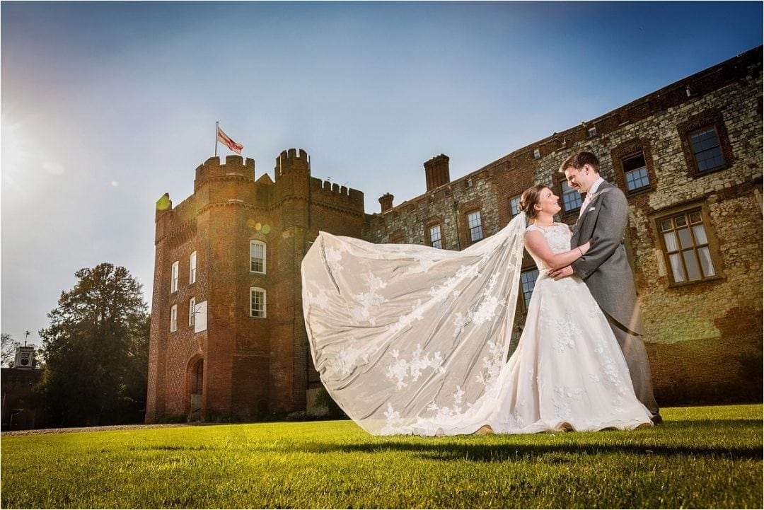 Bride & groom with bride's veil flying backwards in the sun stood outside Farnham Castle, Hertfordshire - Wedding Photography